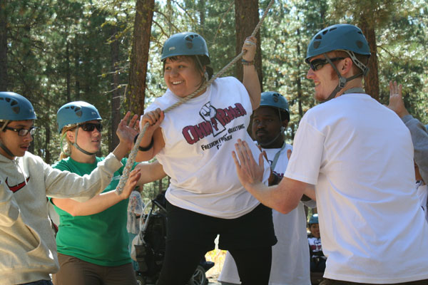 Photo of Dolores uses a rope to balance during the ropes course. Her team stands around her for support.
